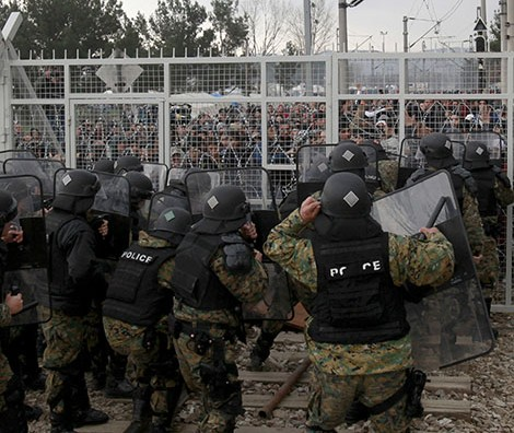 Stranded refugees and migrants, rear, confront Macedonian police, trying to break through the wire fence from the Greek side of the border with Macedonia, near southern Macedonia's town of Gevgelija, Monday, Feb. 29, 2016. Macedonia is restricting the entry of refugees to match the number of those leaving the country, allowing in only refugees from Syria and Iraq, in response to bottlenecks further up along the Balkans migrant route. (AP Photo/Boris Grdanoski)