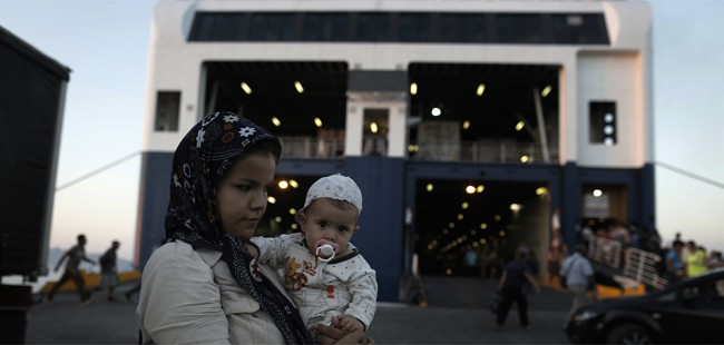 epa04889382 An Afghan refugee holds her baby before boarding a ship to Piraeus, on the island of Kos, Greece, 19 August 2015. The Greek island is struggling with a major influx of refugees and migrants amidst the financial crisis and the height of the tourist season.  EPA/YANNIS KOLESIDIS