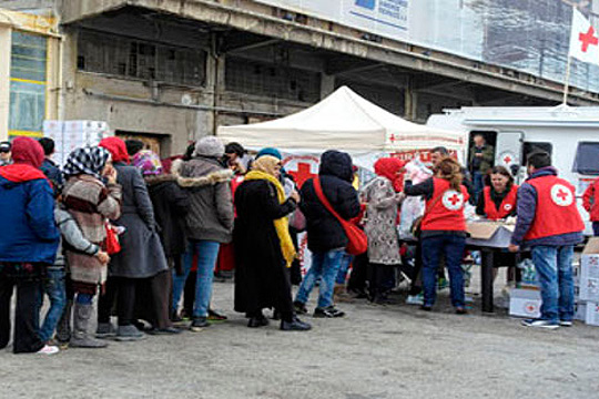 Athens, Greece, 8 March 2016. Thousands of Syrian and Iraqi refugees have been stranded at the port of Piraeus in Athens for several days due to the overcrowded centres in northern Greece. The Hellenic Red Cross provides daily humanitarian aid to those waiting, including food, water, hygiene kits and baby items. Staff and volunteers also man a mobile medical clinic, provide activities for children in the harbour and help people in tracing their lost family members. Caroline Haga/IFRC