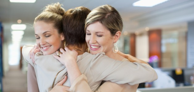 Happy businesswomen hugging in office