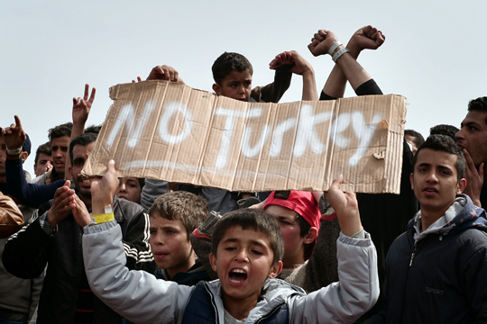 """TOPSHOT - Refugees and migrants including children who left the Chios registration camp, shout slogans and hold placards reading """"'No Turkey"""" during a protest on April  3, 2016 as they camp out in the port of Chios. Greek and EU authorities on April 3, 2016 fine-tuned an operation to expel to Turkey hundreds of migrants denied asylum in a landmark deal slammed by rights groups. Officials declined to comment on the details of the operation, which is believed to begin early Monday from the Greek island of Lesbos where there are over 3,300 refugees and migrants.The operation could involve other Aegean islands with major refugee and migrant populations such as Chios, where agents of EU border agency Frontex were seen arriving on April 3, 2016. / AFP PHOTO / LOUISA GOULIAMAKI"""