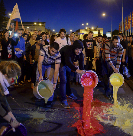 epa05271155 Protesters spill paint on the streets in front of the government building during the protest dubbed 'colorful revolution' against Macedonian President Ivanov's decision on wiretapping amnesty, in Skopje, The Former Yogoslav Republic of Macedonia, 21 April 2016. Ivanov on 12 April decided to abolish all judicial cases related to the big wire-tapping scandal that brought the country to early general elections scheduled for 05 June. The crisis started in 2015 when opposition SDSM started to publish illegally recorded wire-tapped phone conversations of the highest Governmental officials claiming they show financial crime and eventual evidences of electoral frauds of the ruling conservative VMRO-DPMNE party of then PM Gruevski. Gruevski denied everything saying 'foreign intelligence services' are trying to topple his Government he was administrating from 2006. EPA/NAKE BATEV
