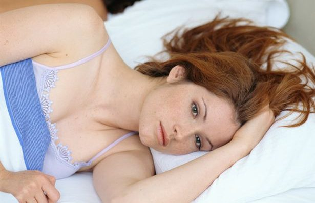 Couple lying in bed, woman with pensive expression on face