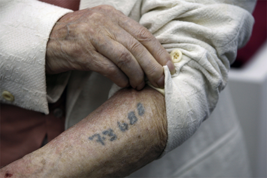 Polish-born Holocaust survivor Hack shows number tattooed on arm during a news conference at the Yad Vashem Museum in Jerusalem