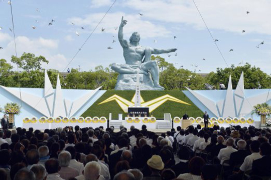 Doves fly over the Statue of Peace during a ceremony at Nagasaki Peace Park in Nagasaki, southern Japan Tuesday, Aug. 9, 2016 to mark the 71st anniversary of the world's second atomic bomb attack. (Ryosuke Uematsu/Kyodo News via AP)