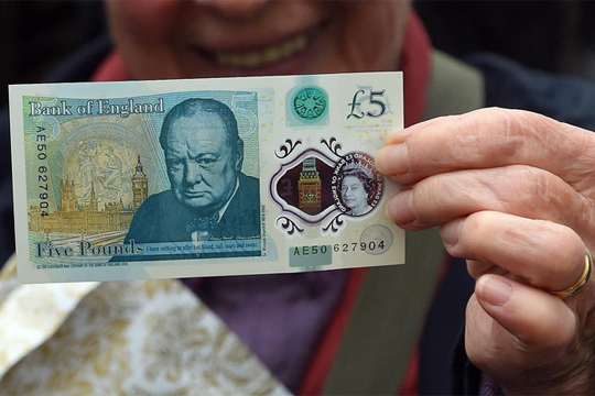 A woman holds up a new £5 (6.5 euros, $7.2) banknote bearing the image of wartime leader Winston Churchill at its unveiling by the Bank of England at Blenheim Palace in Woodstock on June 2, 2016.The note, to be rolled out from September, is the first to be printed on polymer -- a thin, flexible plastic film that is seen as more durable and secure and is already used in Australia and Canada. / AFP PHOTO / POOL / Joe Giddens