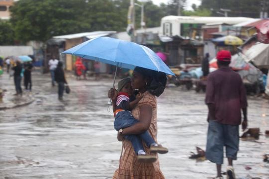 A woman carrying a child walks in the rain triggered by Hurricane Matthew in Port-au-Prince, Haiti, Tuesday, Oct. 4, 2016. Hurricane Matthew roared into the southwestern coast of Haiti on Tuesday, threatening a largely rural corner of the impoverished country with devastating storm conditions as it headed north toward Cuba and the eastern coast of Florida. (AP Photo/Dieu Nalio Chery)