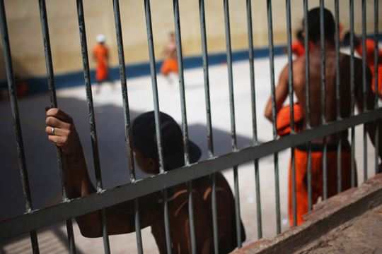 SAO LUIS, BRAZIL - JANUARY 27: Inmates gather in a recreation area in the Pedrinhas Prison Complex, the largest penitentiary in Maranhao state, on January 27, 2015 in Sao Luis, Brazil. Previously one of the most violent prisons in Brazil, Pedrinhas has seen efforts from a new state administration, new prison officials and judiciary leaders from Maranhao which appear to have quelled some of the unrest within the complex. In 2013, nearly 60 inmates were killed within the complex, including three who were beheaded during rioting. Much of the violence stemmed from broken cells allowing inmates and gang rivals to mix in the patios and open spaces of the complex. Officials recently repaired and repopulated the cells allowing law enforcement access and decreasing violence among prisoners, according to officials. Other reforms include a policy of custody hearings and real-time camera feeds. According to officials there have been no prisoner on prisoner killings inside the complex in nearly four months. Critics believe overcrowding is one of the primary causes of rioting and violence in Brazil's prisons. Additionally, overcrowding has strengthened prison gangs which now span the country and contol certain peripheries of cities including Rio de Janeiro, Sao Paulo and Sao Luis. Brazil now has the fourth-largest prison population in the world behind the U.S., Russia and China. The population of those imprisoned had quadrupled in the past twenty years to around 550,000 and the country needs at least 200,000 new incarceration spaces to eliminate overcrowding. A vast increase in minor drug arrests, a dearth of legal advice for prisoners and a lack of political will for new prisons have contributed to the increases. (Photo by Mario Tama/Getty Images)
